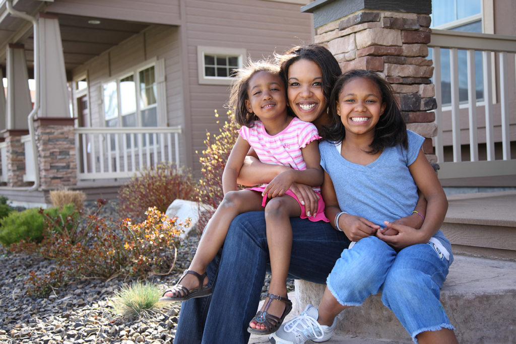 Mom and two daughters in from of new home