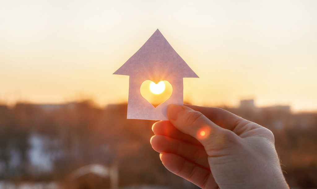 A hand holding up a paper house with a heart cut in the middle and the sun shining through.